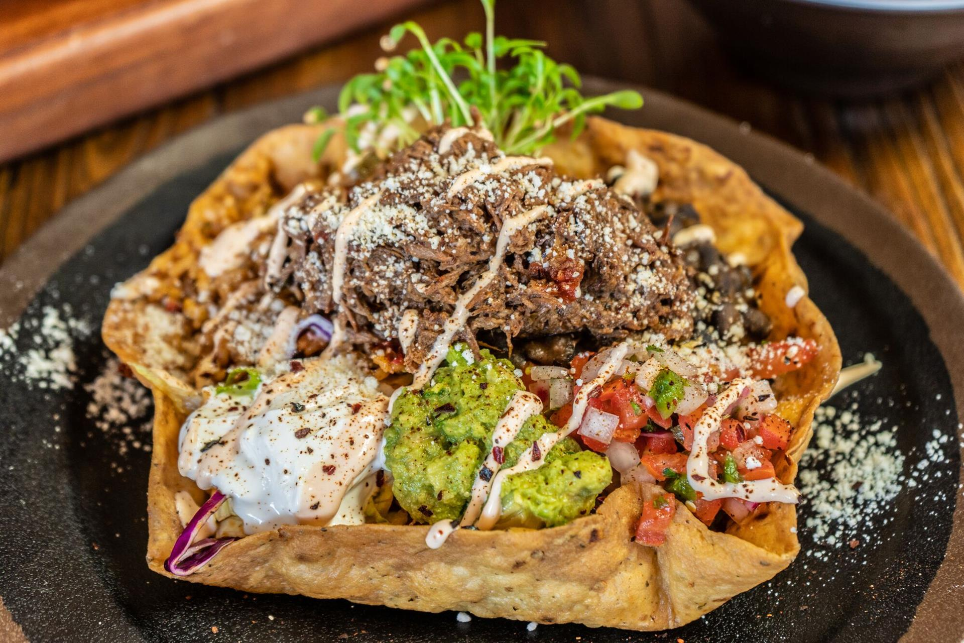 Top shot of Taco salad filled with sourcream, rico de gallo, guacamole, black beans and a choice of meat in a crispy tortilla bowl