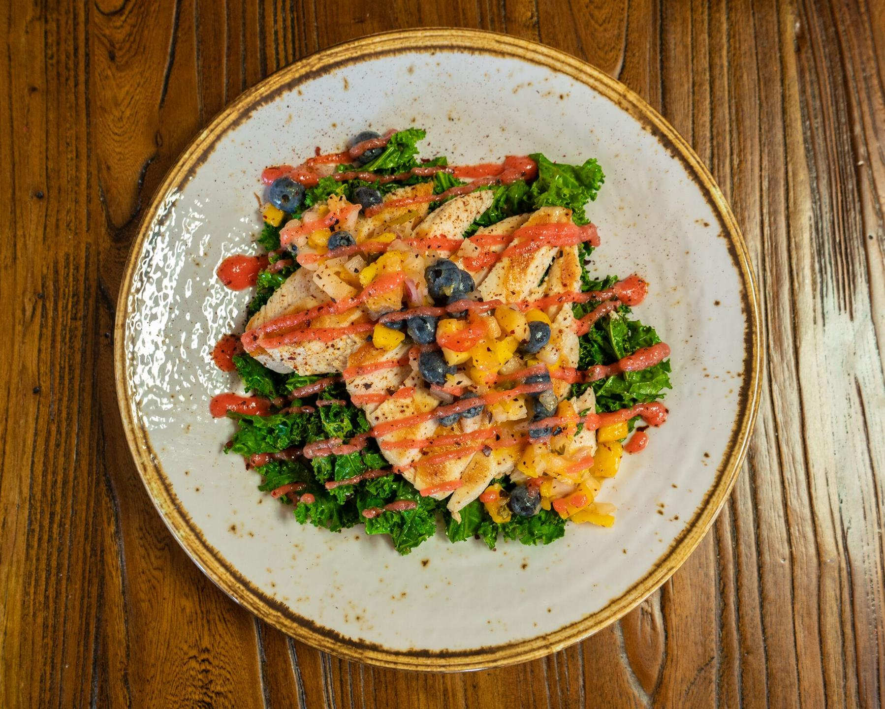 Top shot of Grilled Caribbean spiced boneless chicken topped with tropical blueberry salsa & wilted kale drizzled with habanero-ginger sauce.