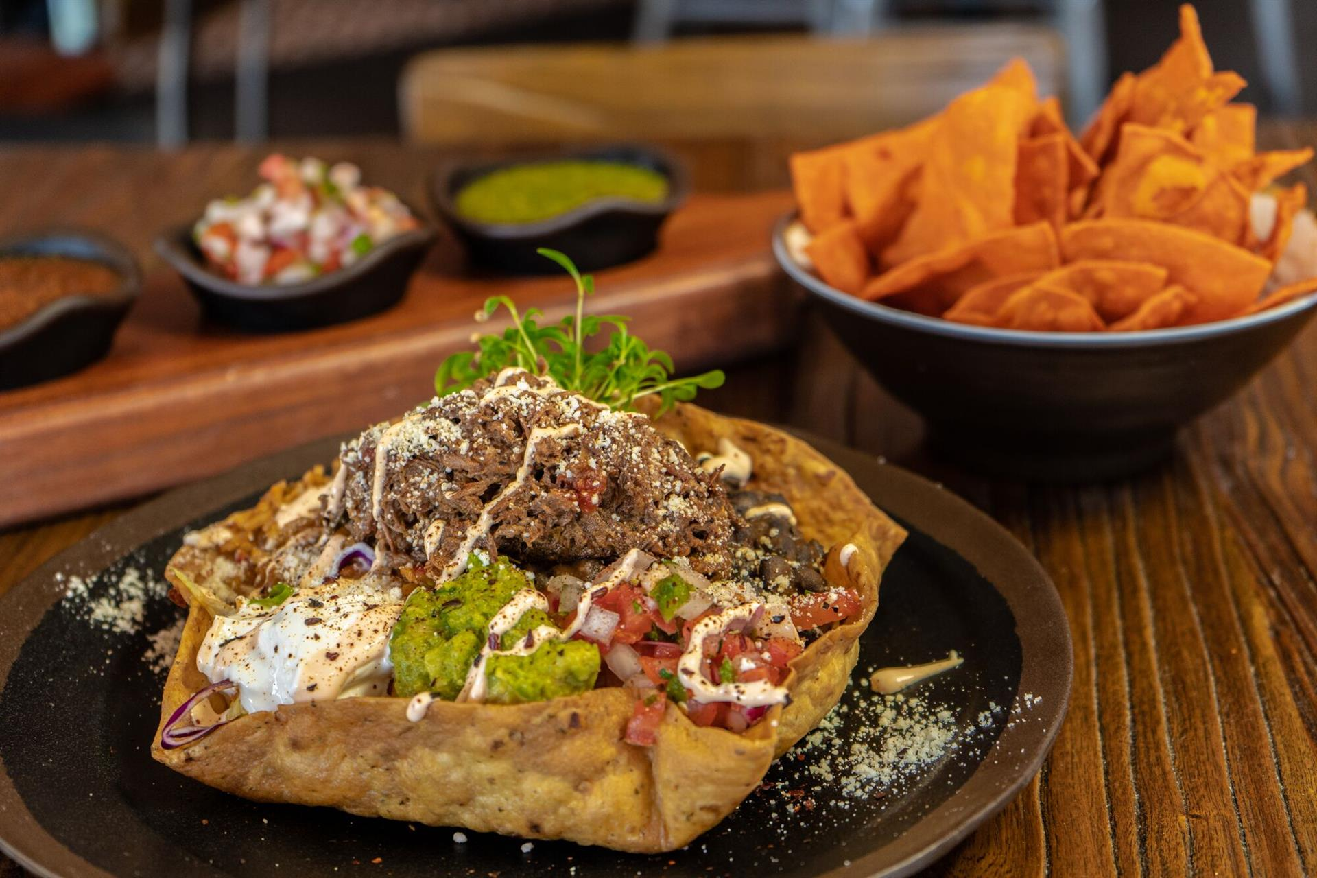 Taco salad filled with sour cream, rico de gallo, guacamole, black beans and a choice of meat in a crispy tortilla bowl next to the trio of salsa and chips