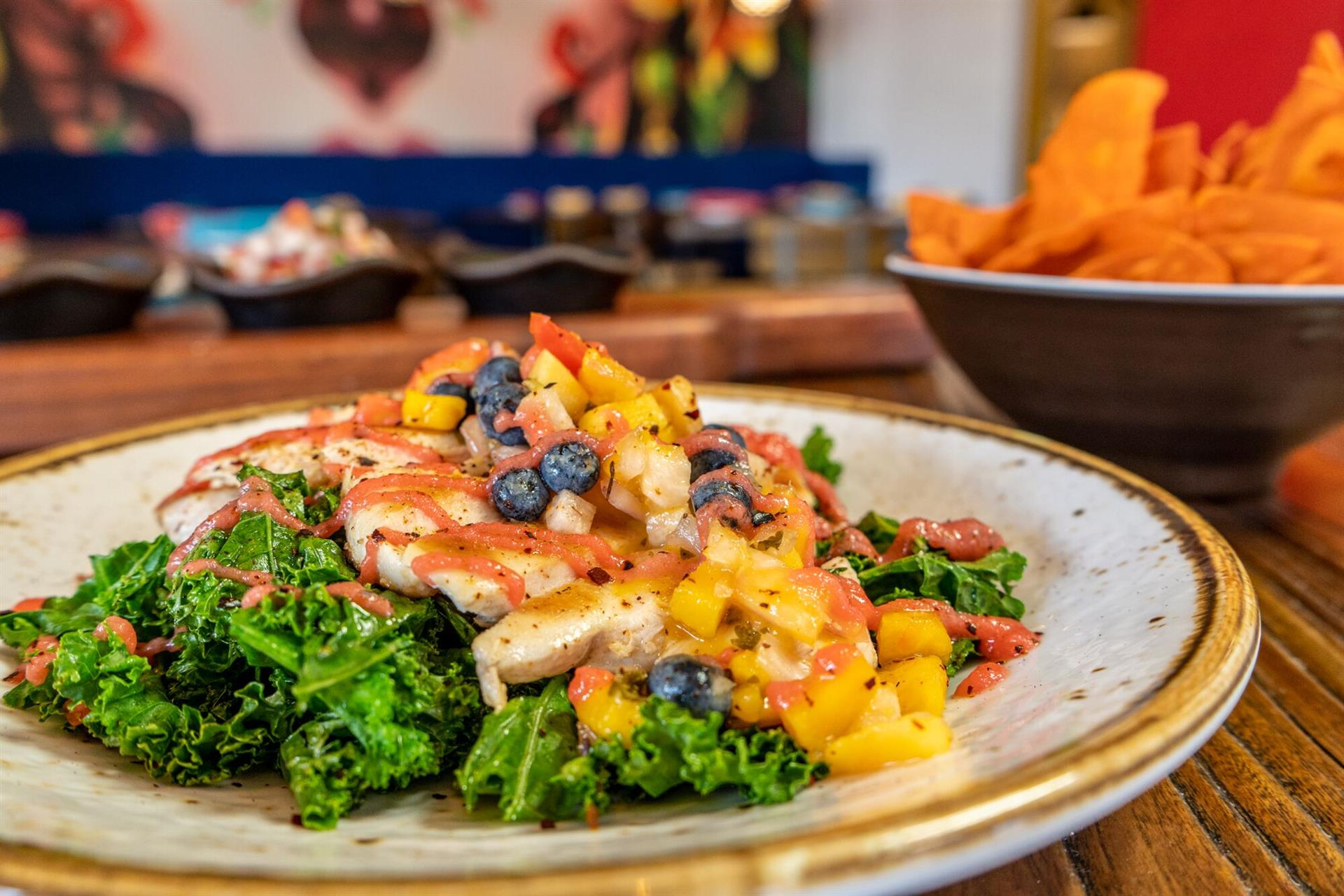 Baja chicken topped with tropical blueberry salsa and wilted kale drizzled harbanero-ginger sauce