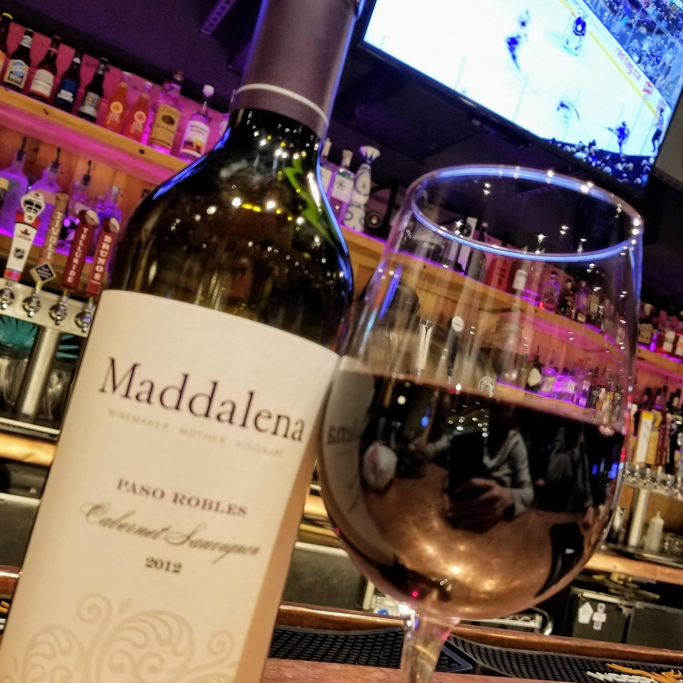 Glass of red wine next to bottle of Maddalena Red Wine on bar