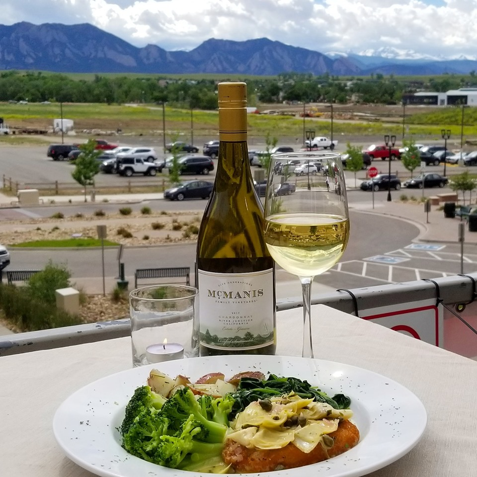 Chicken dish with sauteed vegetables on white plate with glass of white wine with view of mountains