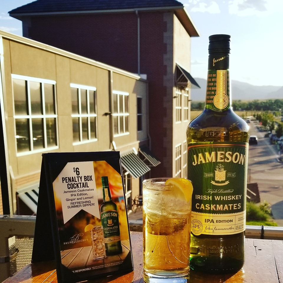 Bottle of Jameson with cocktail on outdoor patio overlooking mountains