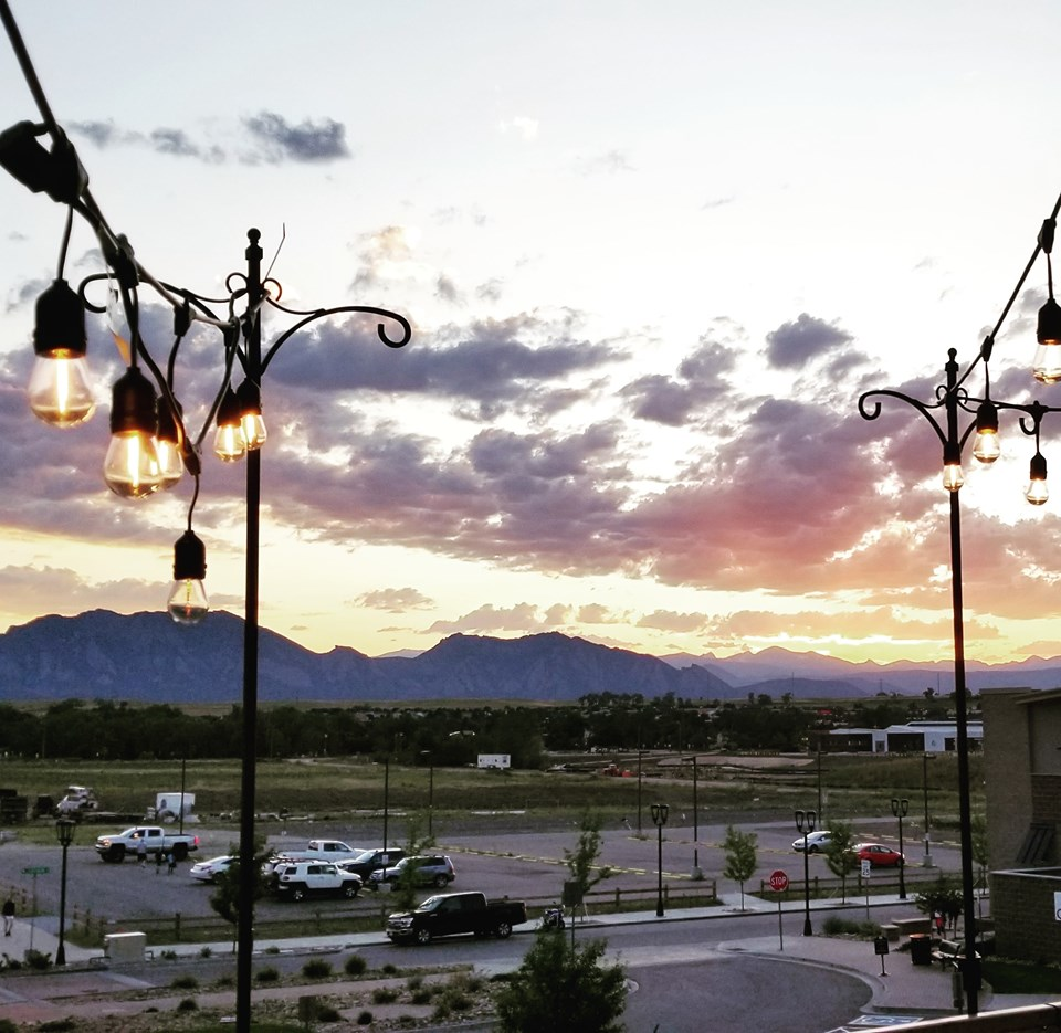 Outdoor patio with string lights overlooking mountain view sunset