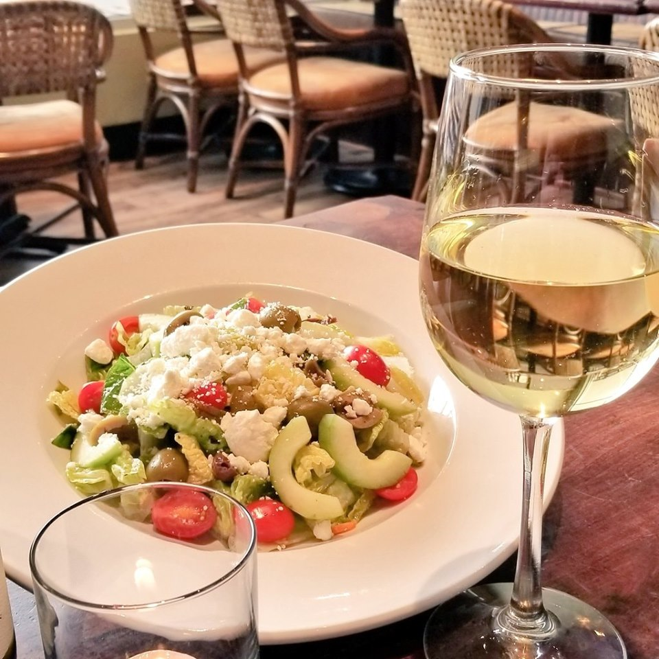 Salad next to glass of white wine on wooden table