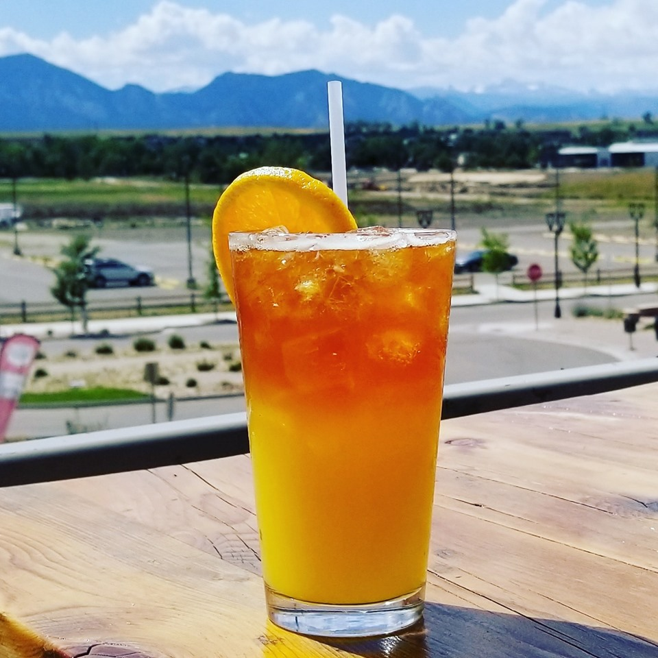 Cocktail with lemon wedge on outdoor patio overlooking mountains