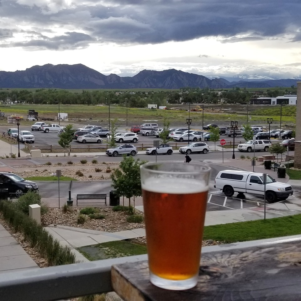 Beer in glass on outdoor patio w overlooking mountains