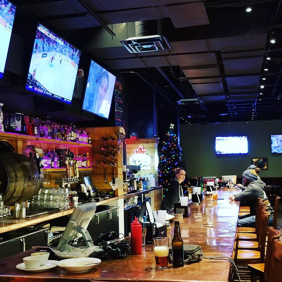 Inside bar with sport games on TV's with colorful lights on small chrismas trees