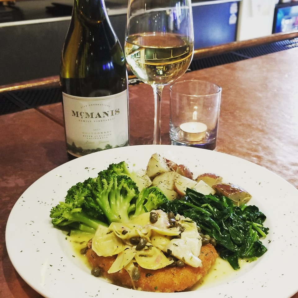 Chicken dish with sauteed vegetables on white plate with glass of white wine