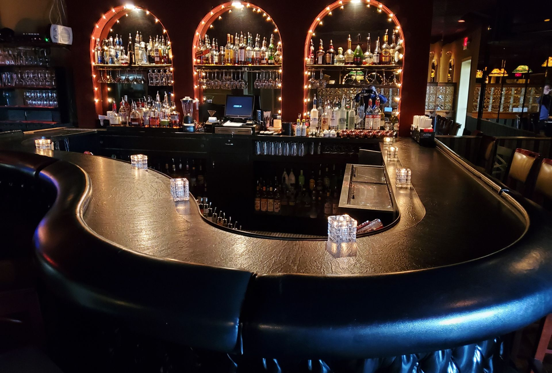 Piano shaped bar with arched lights with shelves of liquor bars inside