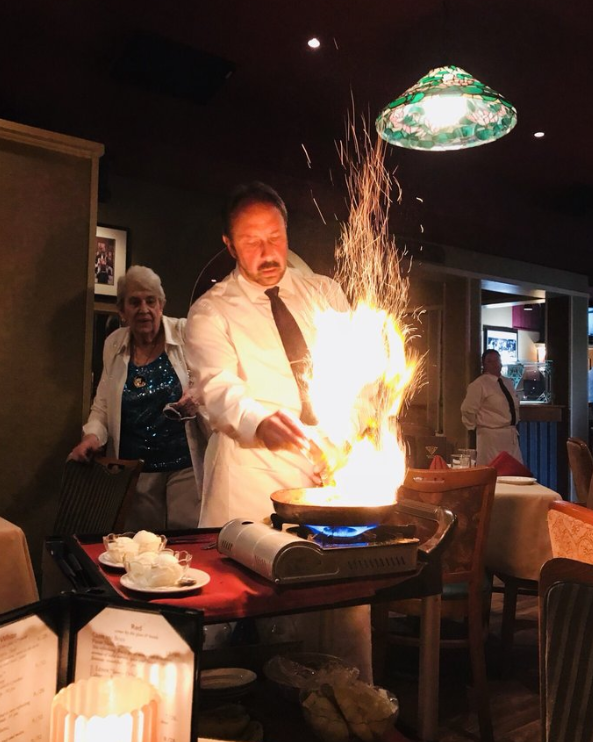waiter preparing bananas foster with fire on the pan