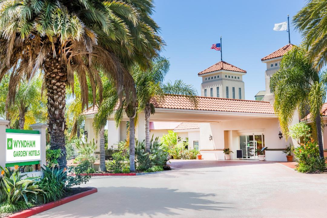 exterior shot of san joe airport wydham garden with palm trees and lush foliage
