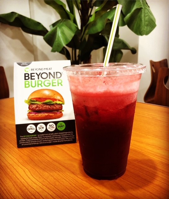 juice in a to go cup on a table in front of a sign about the Beyond Burger