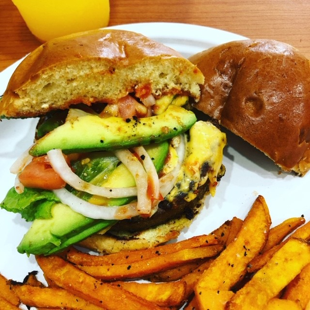 sandwich with avocado, onions and tomato on a bun with a side of fries