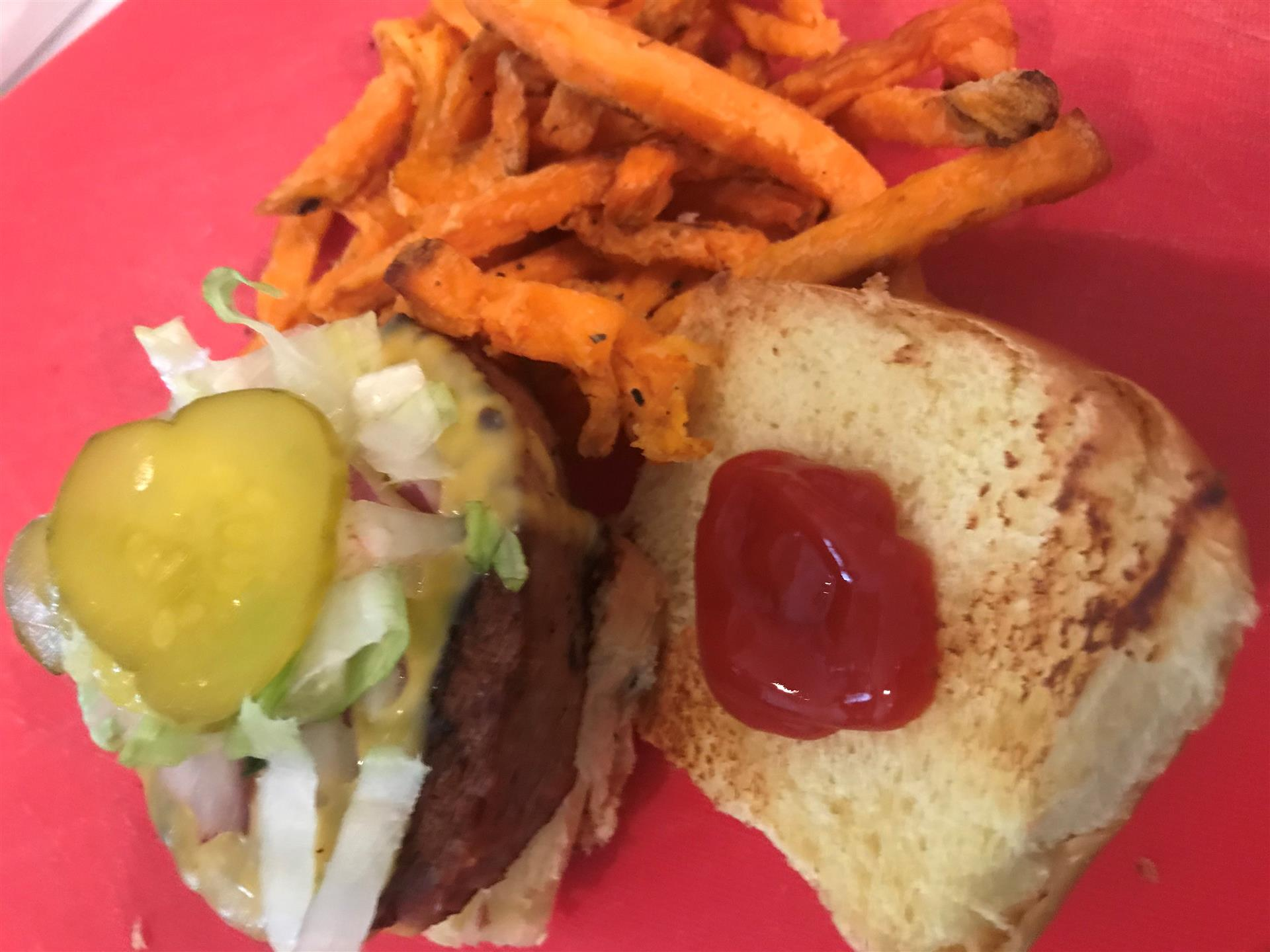 beyond burger with pickles and ketchup with a side of sweet potato fries & a snapple