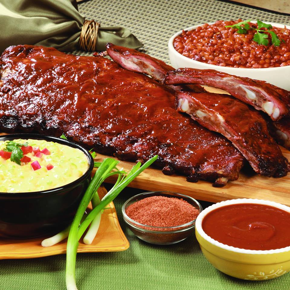 meat on wood, surrounded by a bowl of beans, a bow of bbq sauce, a bowl of seasoning and celery stalks