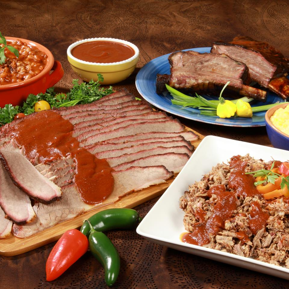 sliced meat with barbecue sauce drizzled on top, next to a bowl of refried beans, a bowl of barbecue sauce, a plate of ribs and a plate of shredded meat with barbecue sauce drizzled on top