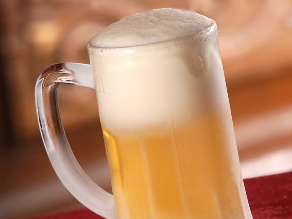 beer mug filled with beer and foam at the top