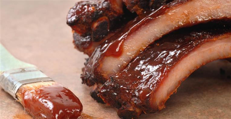 ribs next to a brush with bbq sauce