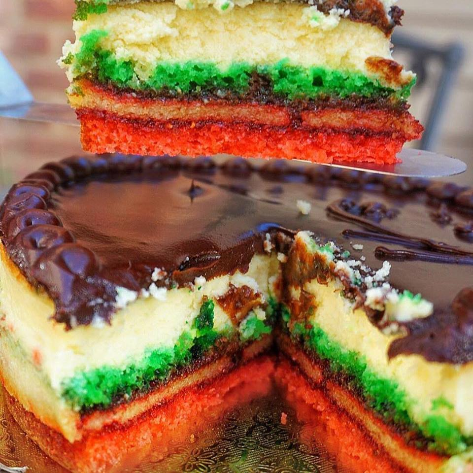 a rainbow cookie cake with a slice missing