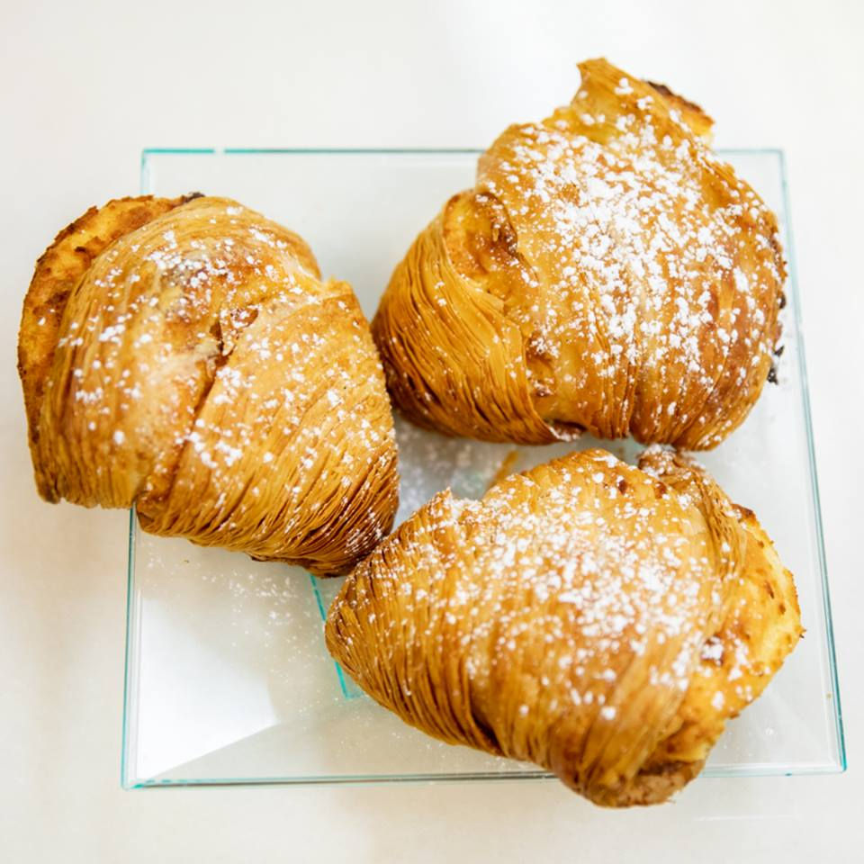 Three croissants covered in powdered sugar