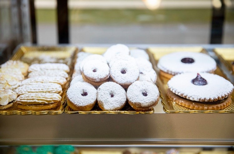 A varietion of different pastries covered in powdered sugar