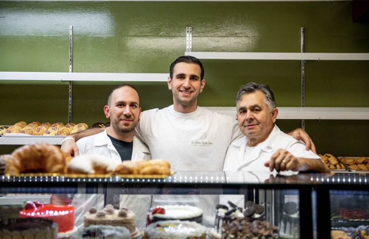 La Roma Pastry Family Employees standing behind the display of cakes and croissants
