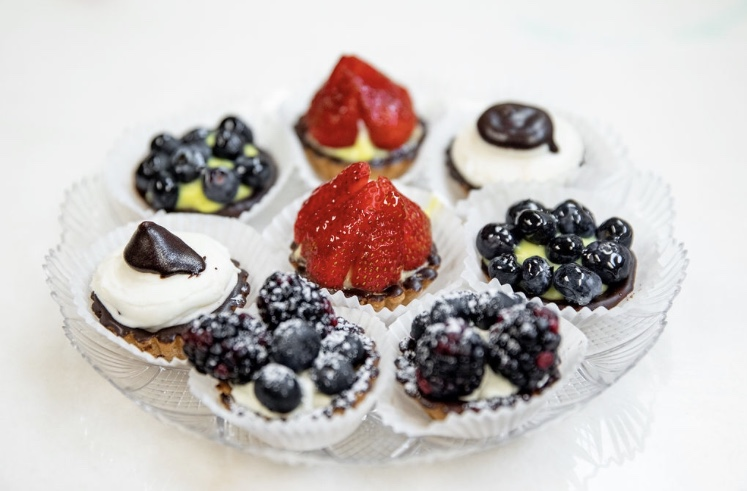 assortment of desserts with blueberries, and strawberries on top