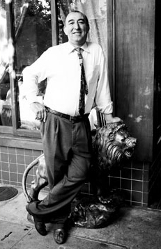 Vintage photo of man lening on metal lion statue