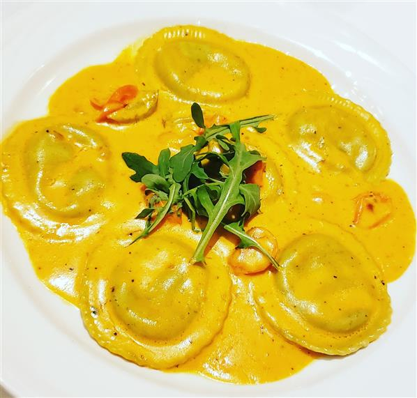 Spinach Ravioli. Pasta stuffed with spinach and ricotta cheese topped with vodka pink sauce