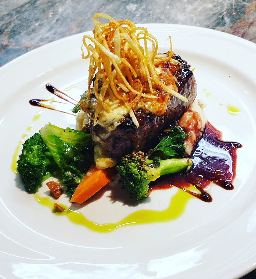 Filet Mignon. Char broiled New York steak, served with red wine and black peppercorn sauce over mixed veggies