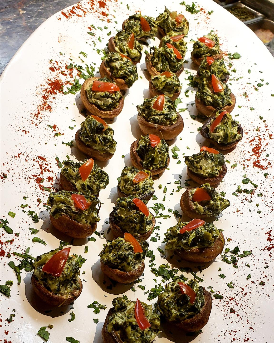 Three rows of stuffed mushrooms on a plate.