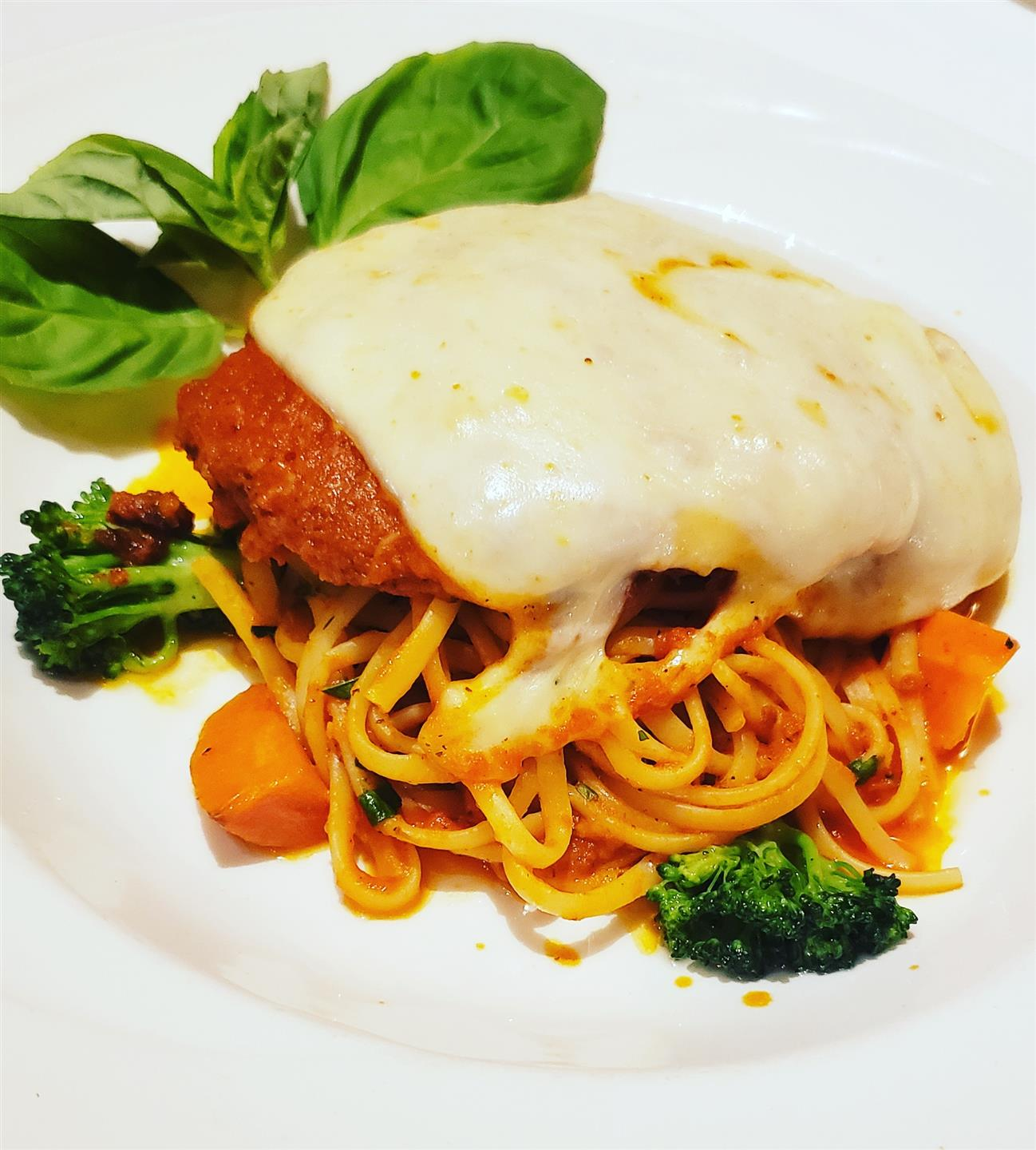 Parmesan Chicken. Chicken breast breaded and topped with marinara sauce and mozzarella cheese baked until bubbly. Served with fresh linguine pasta and seasonal vegetables