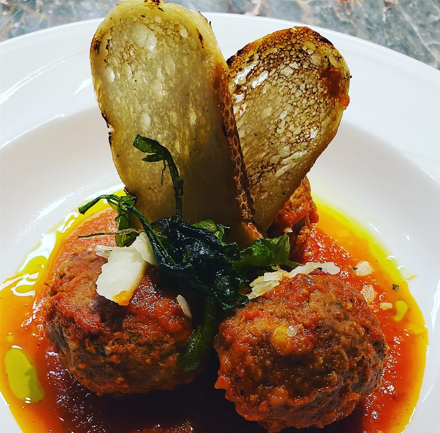 Polpette Della Mamma. Homemade Wagyu beef meatballs topped with tomato sauce and toasted slices of bread