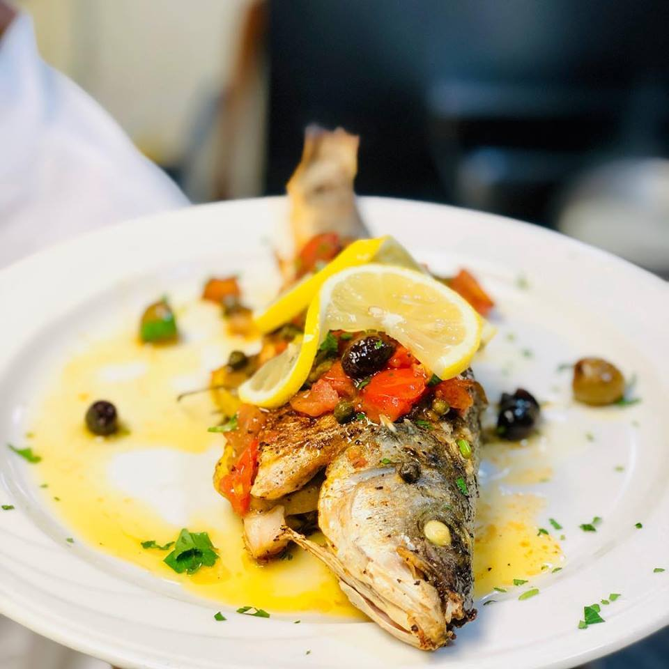 Whole fish on plate with lemon slice