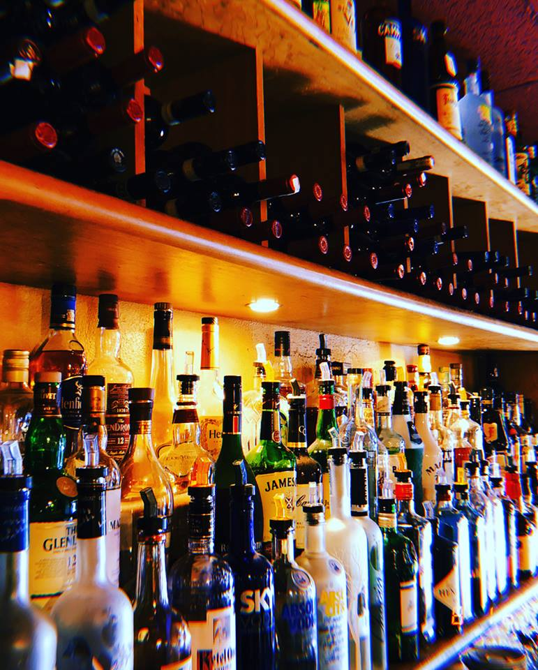 shelves stocked with assorted liquor bottles behind the bar.