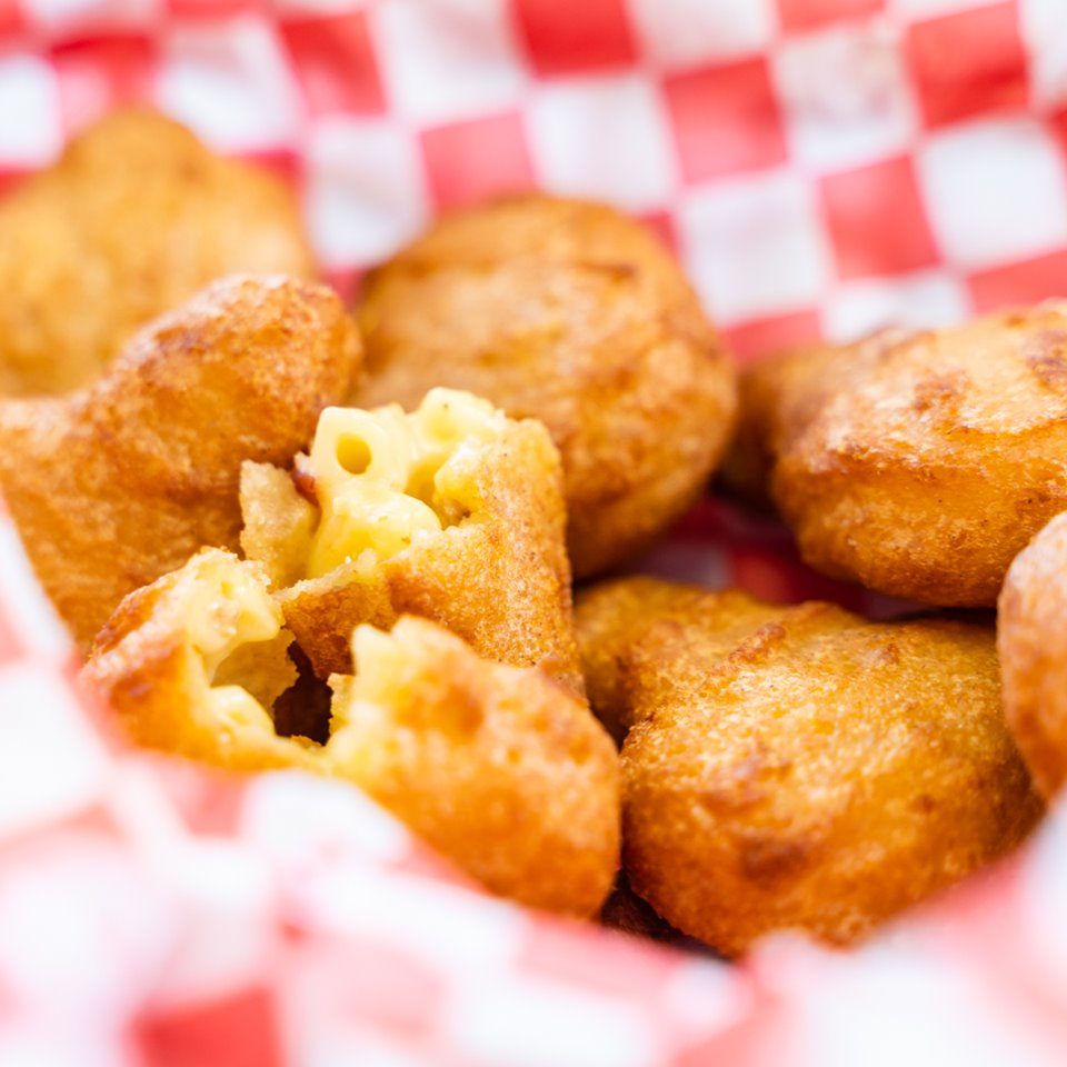 Deep fried mac n cheese balls in checkered-pattern paper bowl
