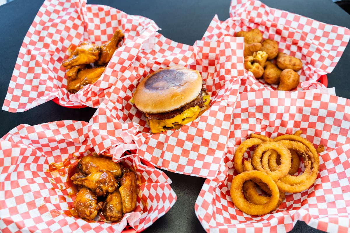 Variety of wings, onion rings, and burgers in paper holders with checkered pattern paper