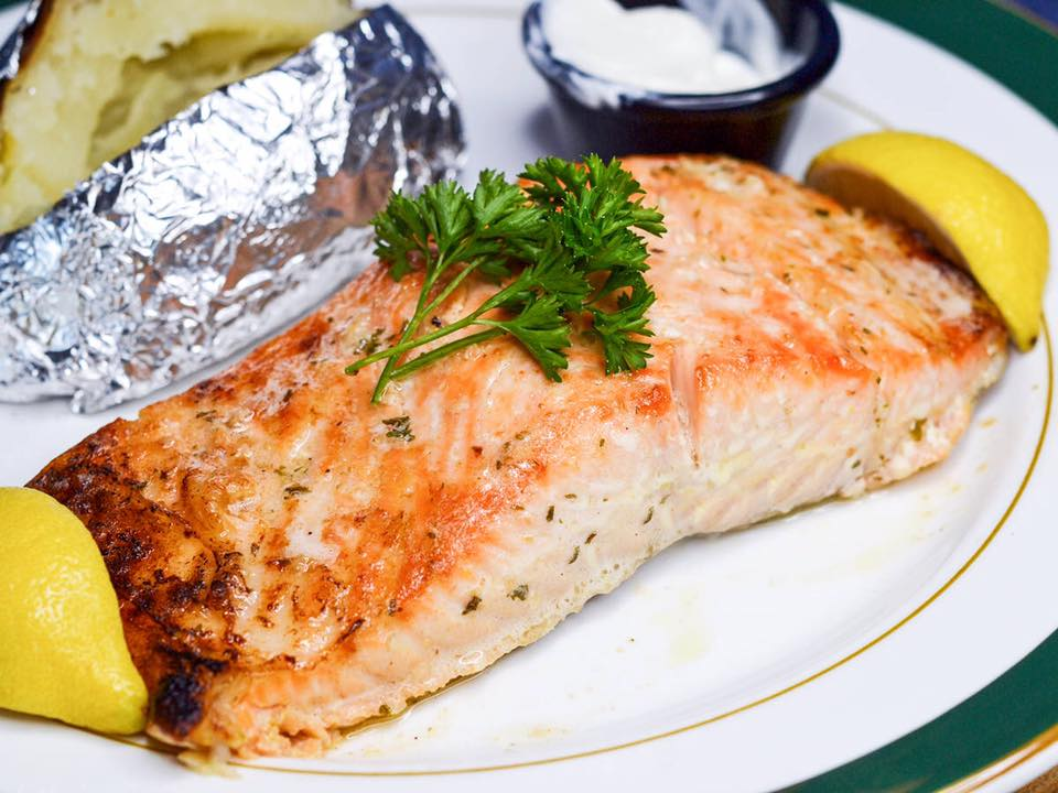 filet of salmon with a baked potato and parsley on top