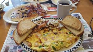 ham and soinach omelet with hashbrowns on toast, next to a plate of pancakes and bacon