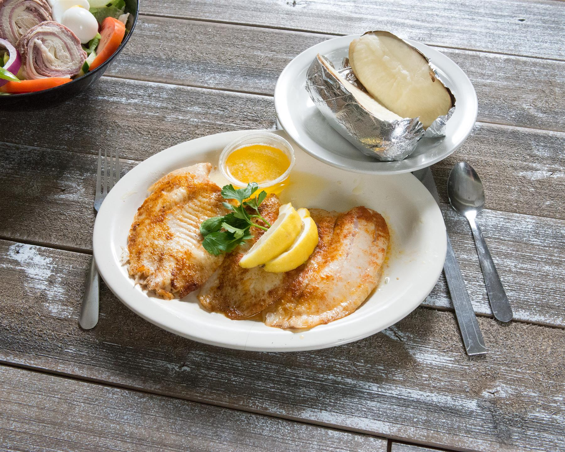 fish with lemon and butter and a baked potato