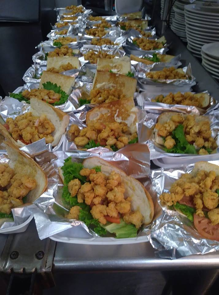 A table filled with premade sandwiches with fried shrimp poboys