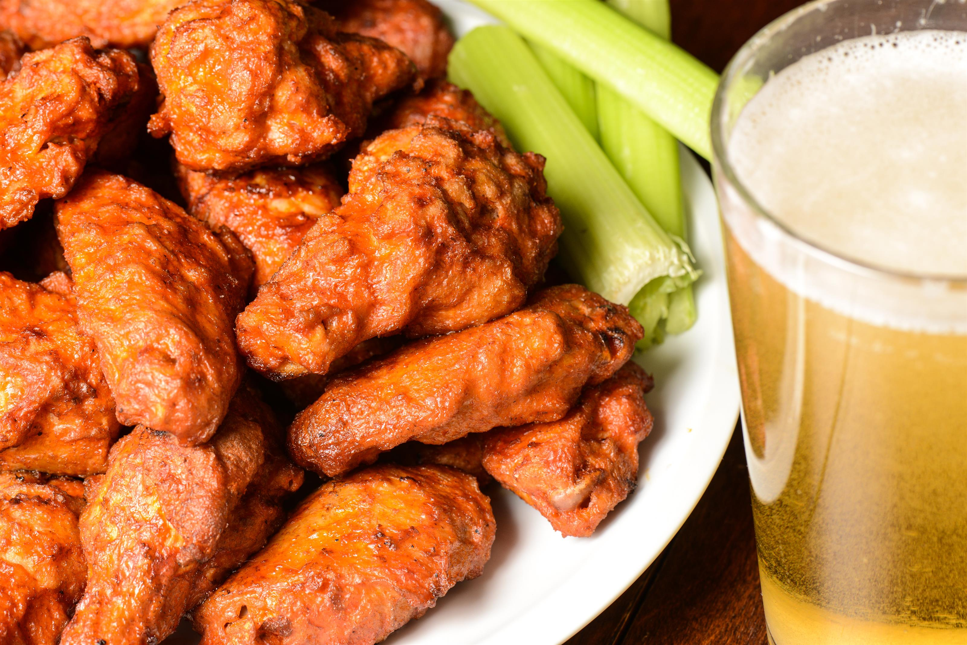 buffalo wings with a side of celery and a  pint of beer