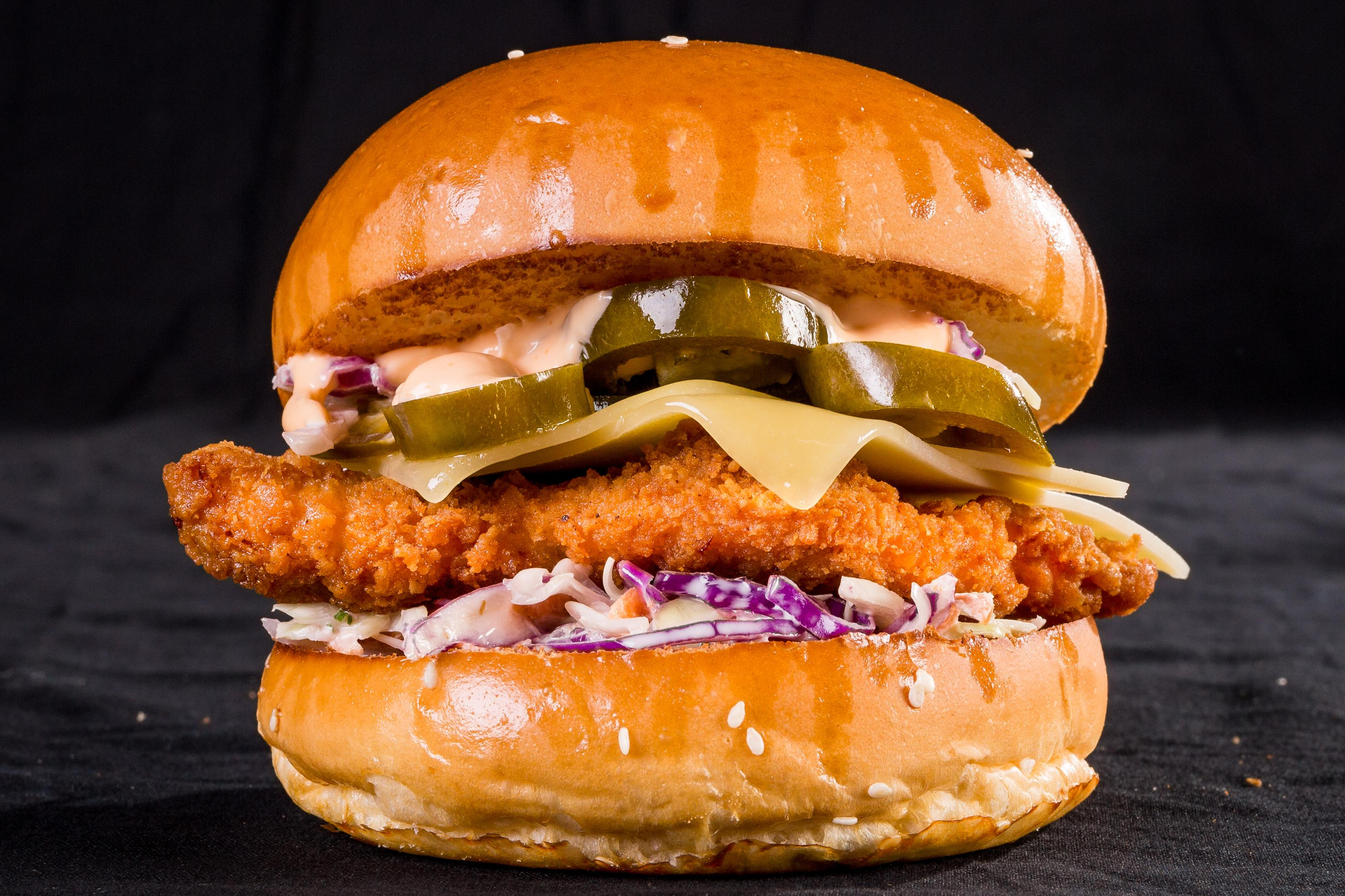 spicy chicken sandwich with lettuce, tomato, cheese, red onion, pickles, slaw, and a homemade sauce