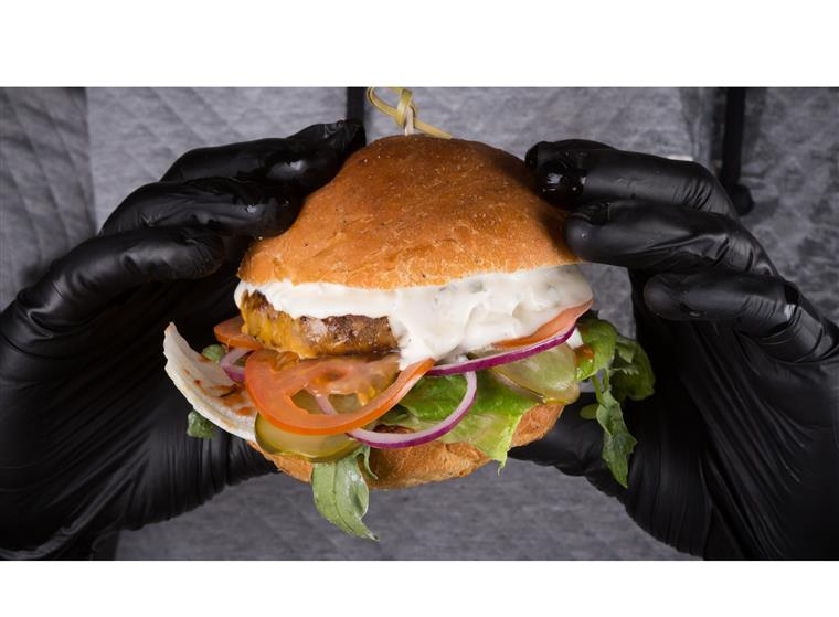 someone holding the meszsy fun burger with black gloves