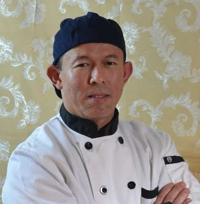 Chef in white shirt crossing arms with hat on