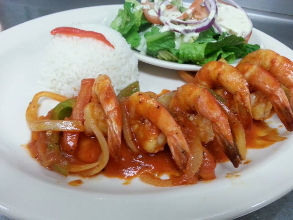 Shrimp lined up on a white plate with scoop of rice