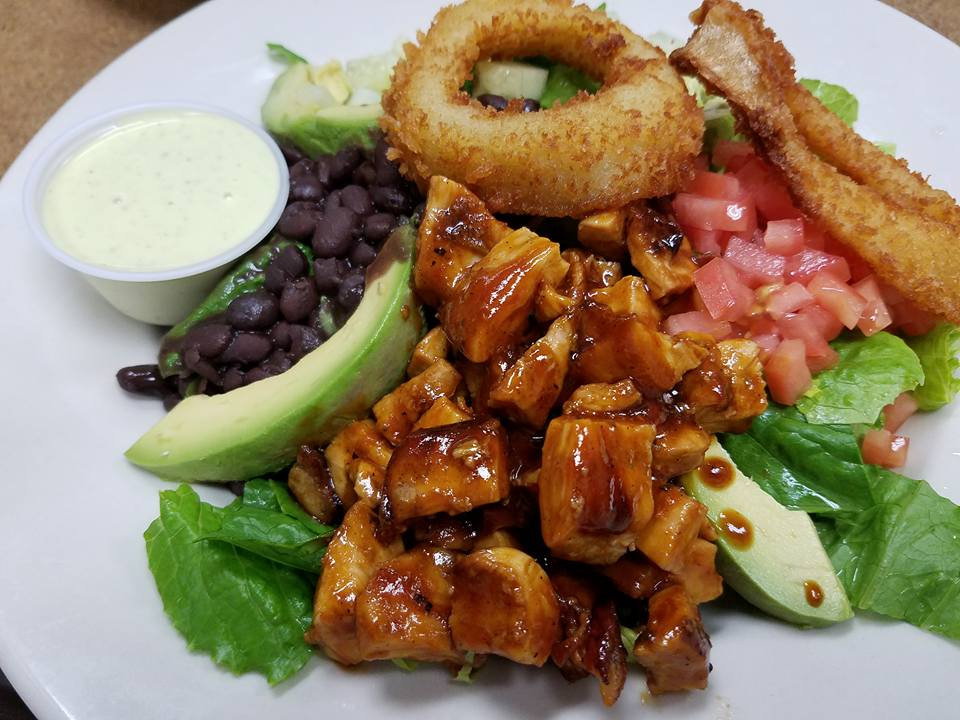 Marinated sliced meat mixed with avocado, lettuce, and onion rings
