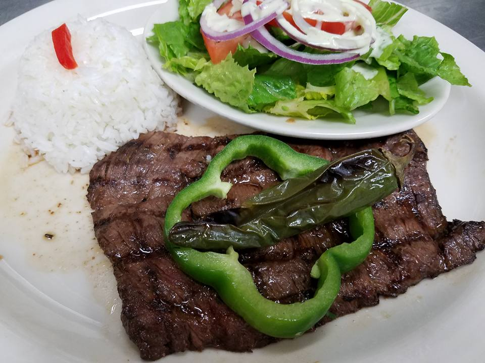 Steak on white plate with slice of bell pepper with roasted finger pepper on top