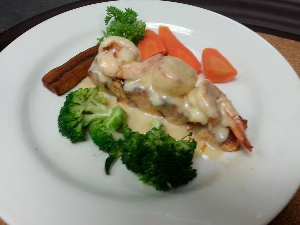 Salmon on a white plate with shrimp on top in a sauce